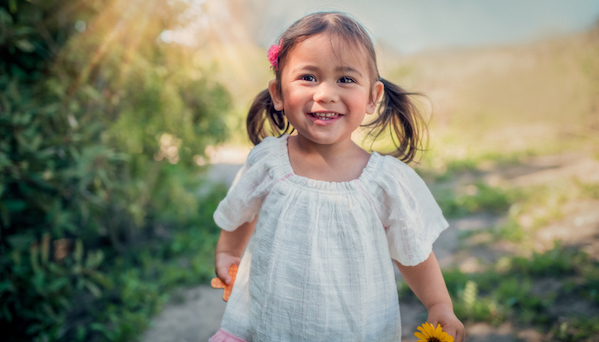 A 2 year old girl smiles as she plays outdoors carrying the letter X and a yellow daisy.